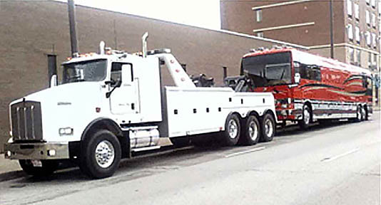 Heavy Duty Tow Truck hauling Tour Bus Recreational Vehicle